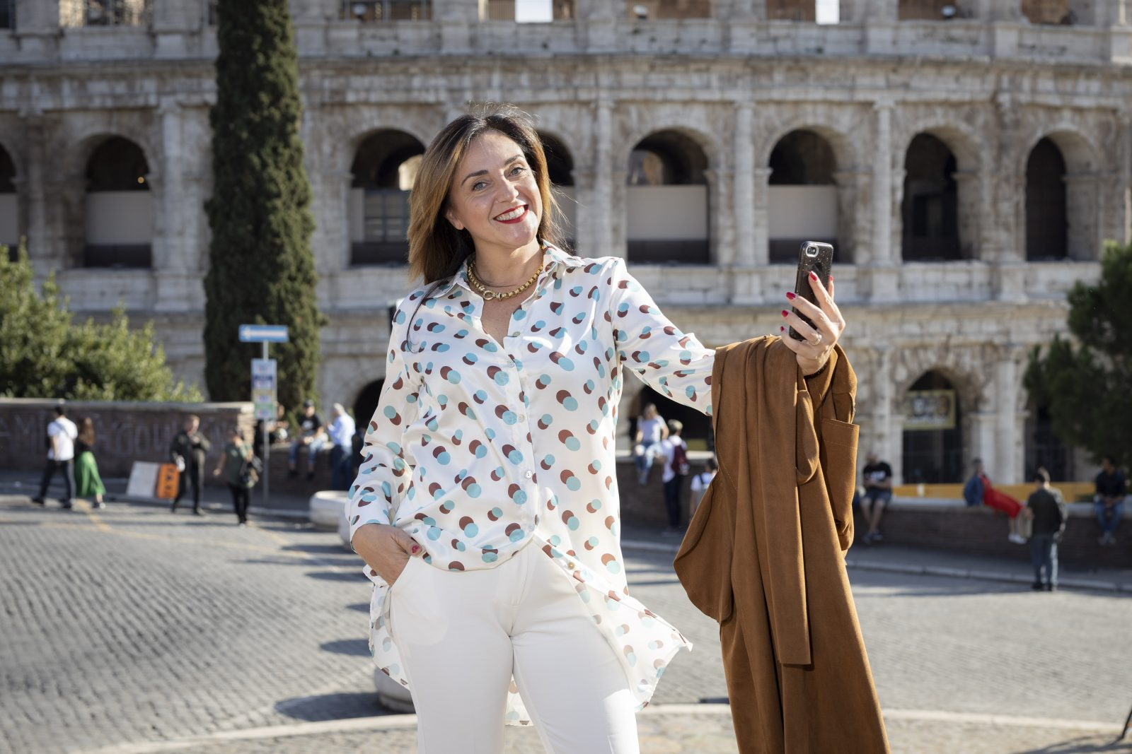 Silvia Rossi con uno smartphone per le vie del centro di Roma. La foto illustra come il futuro del Real Estate sia sempre più social. Ecco come usar ei social media per vendere casa.